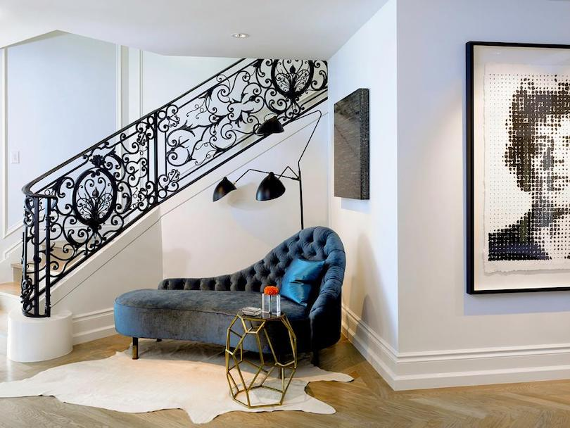 Entryway With Plush Chaise and Intricate Railing
